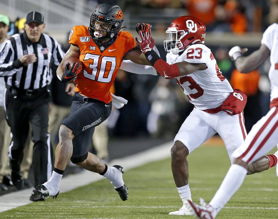 Photo - Oklahoma's DaShaun White (23) pushes Chuba Hubbard (30) out of bounds in the fist quarter during the Bedlam college football game between the Oklahoma State Cowboys (OSU) and Oklahoma Sooners (OU) at Boone Pickens Stadium in Stillwater, Okla., Saturday, Nov. 30, 2019. OU won  34-16. [Sarah Phipps/The Oklahoman]