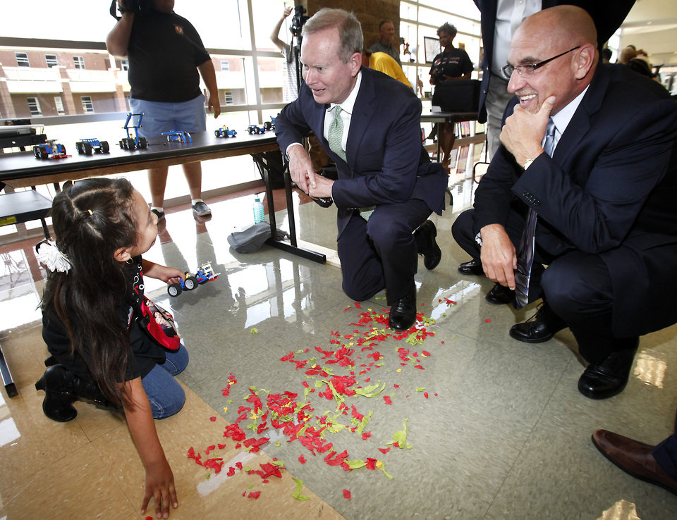 Photo - Third grader Evelin Lopez shows  OKC Mayor Mick Cornett and OKCPS Superintendent Rob Neu her sweeper car she made in science class during a tour of a summer learning program sponsored by the city of Oklahoma City and the school district., Thursday, July 3, 2014. About 70 kids from F.D. Moon Elementary School are participating in a Summer Steam Academy at Douglass Mid-High School that focuses on science, technology, engineering, arts and math and offers rigorous reading intervention.   Photo by David McDaniel, The Oklahoman