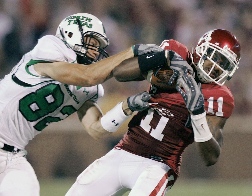 Photo - Oklahoma defensive back Lendy Holmes (11) intercepts a pass intended for North Texas receiver Brock Strickler (82) in the second half during the University of Oklahoma Sooners (OU) college football game against the University of North Texas Mean Green (UNT) at the Gaylord Family - Oklahoma Memorial Stadium, on Saturday, Sept. 1, 2007, in Norman, Okla.