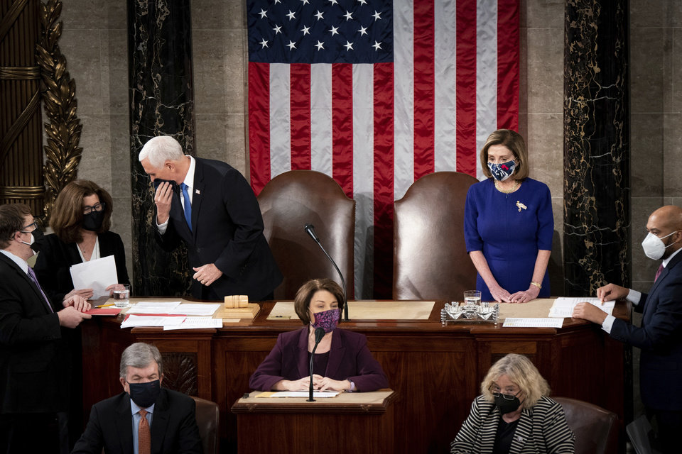 Photo - Speaker of the House Nancy Pelosi, D-Calif., and Vice President Mike Pence preside as a joint session of the House and Senate convenes to count the Electoral College votes cast in November's election, at the Capitol in Washington, Wednesday, Jan. 6, 2021. (Erin Schaff/The New York Times via AP, Pool)
