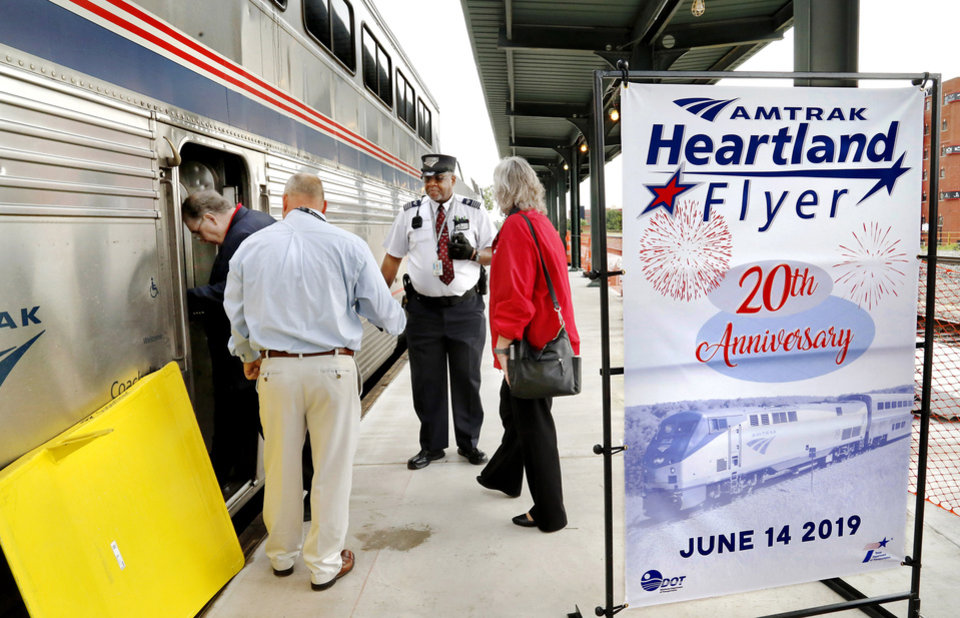 Photo - Passengers step onto Amtrak's Heartland Flyer train as conductor Dwayne Shaw greets them during boarding at Santa Fe Depot in downtown Oklahoma City Friday morning, June 14, 2019. The Heartland Flyer is celebrating its 20th year of serving rail passengers in Oklahoma and Texas.  The daily service by Amtrak has carried more than 1.4 million passengers between Oklahoma City and Fort Worth during the past two decades. Originating its route on Oklahoma City, the Heartland Flyer connects to the Texas Eagle train in Fort Worth, which provides service to major cities including Dallas, Little Rock, St. Louis or Austin and San Antonio. [Jim Beckel/The Oklahoman]