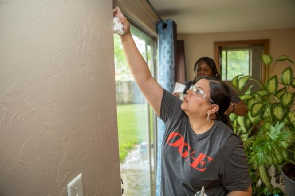 Photo -  OG&E volunteers Jeanette Staden and Stephanie Coleman work on weatherizing a patio door as part of the utility's Silver Energy Sweep initiative in south Oklahoma City. The utility and partnering nonprofits are making improvements to more than 170 customers' homes as part of the sweep, utility officials say.