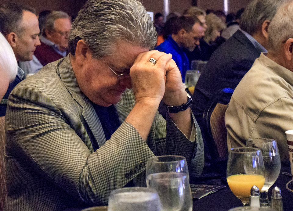 Photo - Bill Wolfe lowers his head in prayer during the CBMC Metro Prayer Breakfast at the Cox Convention Center in Oklahoma City, Okla. on Tuesday, April 16, 2019.   Photo by Chris Landsberger, The Oklahoman