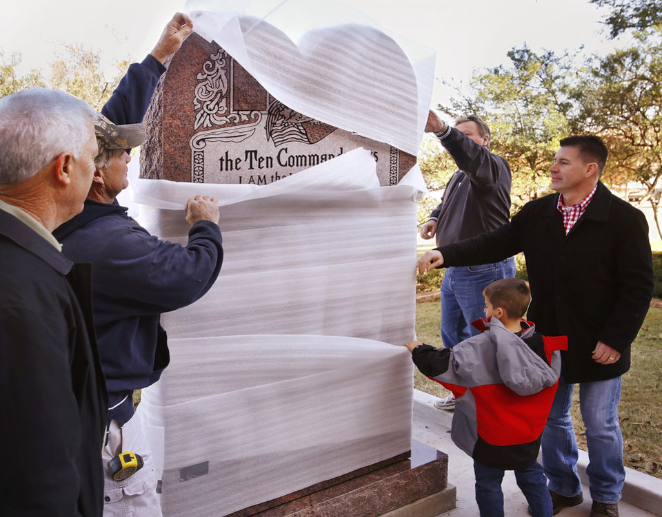 Photo - Rep. John Bennett, Sallisaw, far right and his son, Nicholas, 5, help remove protective covering from the statue after it was erected. At far left is Rep. Mike Reynolds.  A six-foot tall granite monument of the Ten Commandments  is erected on the north side of the state Capitol grounds Thursday morning, Nov. 15, 2012.  Photo by Jim Beckel, The Oklahoman