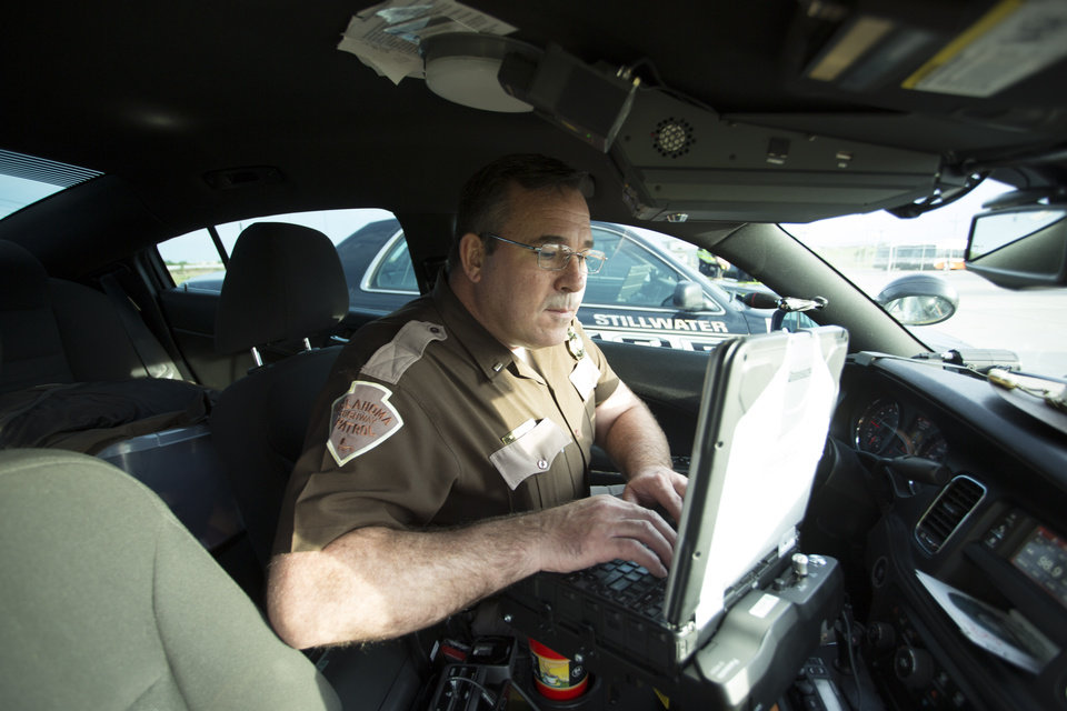 Photo - Trooper Joe Williams checking information during a recent ENDUI checkpoint. Photo: J Pat Carter