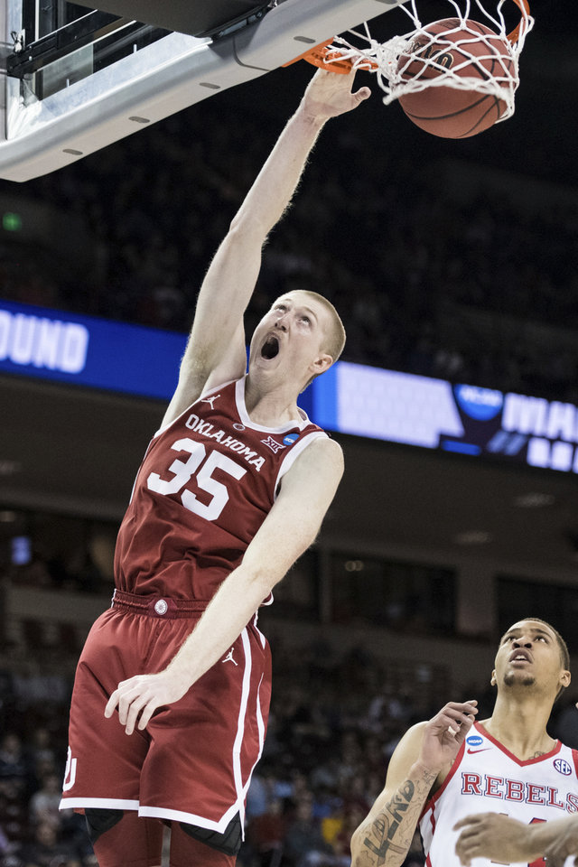 Photo - Oklahoma forward Brady Manek (35) dunks the ball as Mississippi forward KJ Buffen, right, looks on during a first round men's college basketball game in the NCAA Tournament Friday, March 22, 2019, in Columbia, S.C. (AP Photo/Sean Rayford)