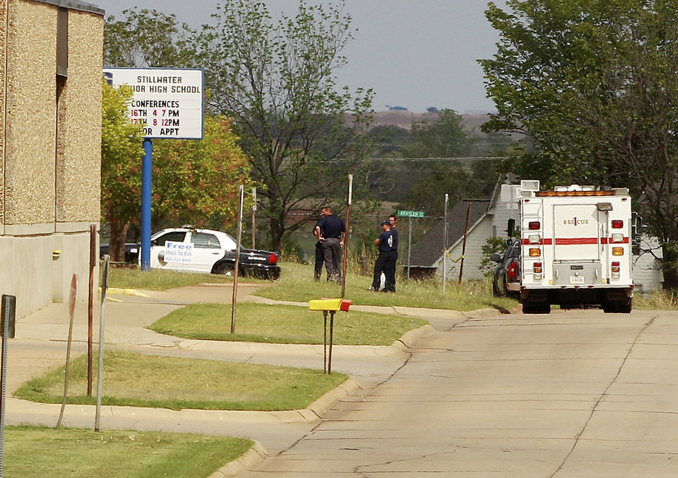 Photo - A fire-rescue truck  and a police car are parked outside Stillwater Junior High School in Stillwater, Okla., Wednesday, Sept. 26, 2012. A 13-year-old student shot and killed himself in a hallway at an Oklahoma junior high school before classes began Wednesday, police said, terrifying teenagers who feared a gunman was on the loose. (AP Photo/Sue Ogrocki) ORG XMIT: OKSO107