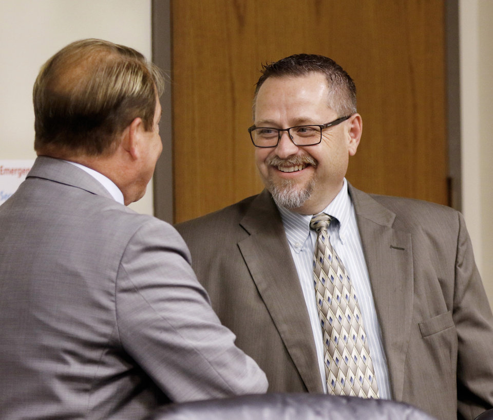 Photo - Timothy Starkey, board president, right, greets Dr. Charles Grim. The Oklahoma State Department of Health voted at their monthly meeting Tuesday morning, July 10, 2018, to ban sales of smokeable forms of medical marijuana and to require dispensaries to hire a pharmacist. The Board of Health voted on 75 pages of rules creating a rough framework for patients, physicians, caretakers and business owners interested in medical marijuana. The ban on sales of leaves and flowers for smoking and the requirement to hire a pharmacist weren't in the draft rules presented to the board, but were a priority of a coalition of medical groups. Julie Ezell, the Health Department's general counsel, presented the rules to a packed board room and to members of the public watching in an overflow room and online. She cautioned board members that the two new rules they added might not be allowed under the state question, inviting a court challenge. Photo by Jim Beckel, The Oklahoman