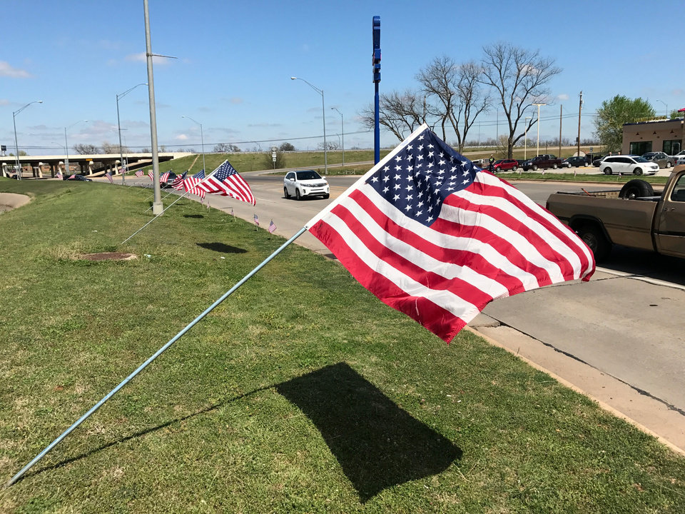 Photo - Flags line the route into downtown Tecumseh Monday afternoon. Townspeople are gathering in parking lots and on curbs holding flags and balloons out of respect for Tecumseh PD officer who was shot and killed while performing a traffic stop overnight.  Photo by Jim Beckel