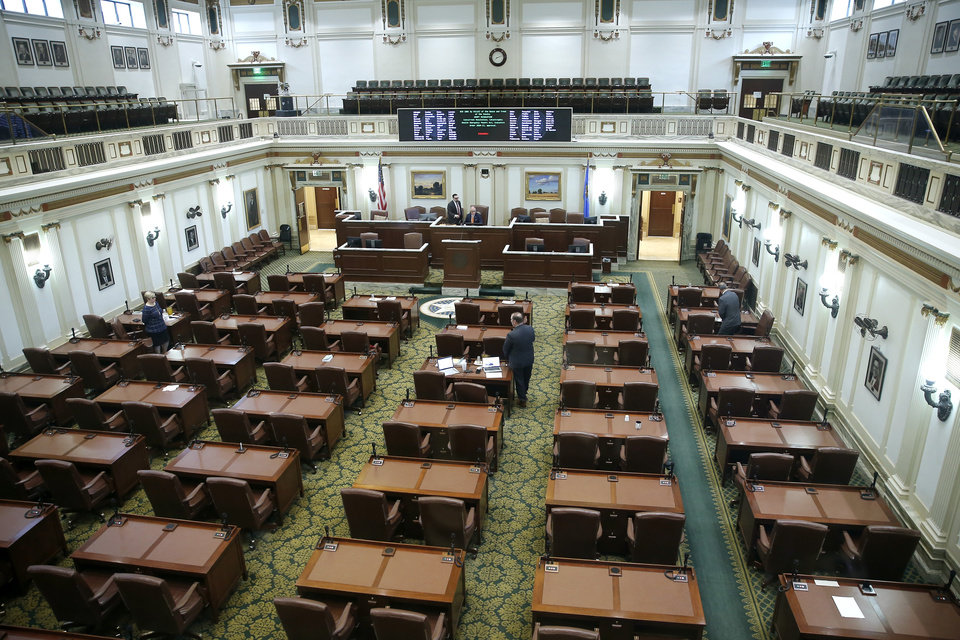 Photo - A  skeleton crew of lawmakers inside the House chamber during a special session of the House of Representatives at the state Capitol in Oklahoma City, Monday, April 6, 2020. A skeleton crew of lawmakers was allowed in the House chamber as others watched from their offices during a special session of the House of Representatives. [Bryan Terry/The Oklahoman]
