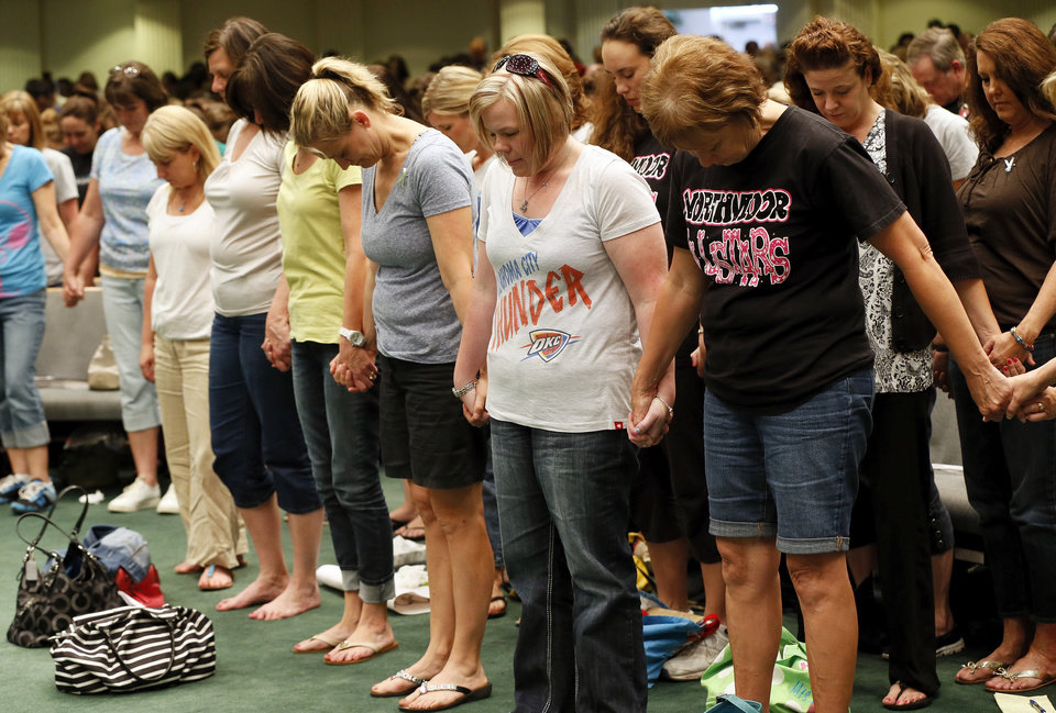 Photo - Moore educators stand together and pray at the end of a district-wide meeting of Moore Public Schools employees at Southern Hills Baptist Church, 8601 Pennsylvania Ave., in Oklahoma City, Wednesday, May 22, 2013, after a tornado struck south Oklahoma City and Moore, Okla., on Monday. Photo by Nate Billings, The Oklahoman