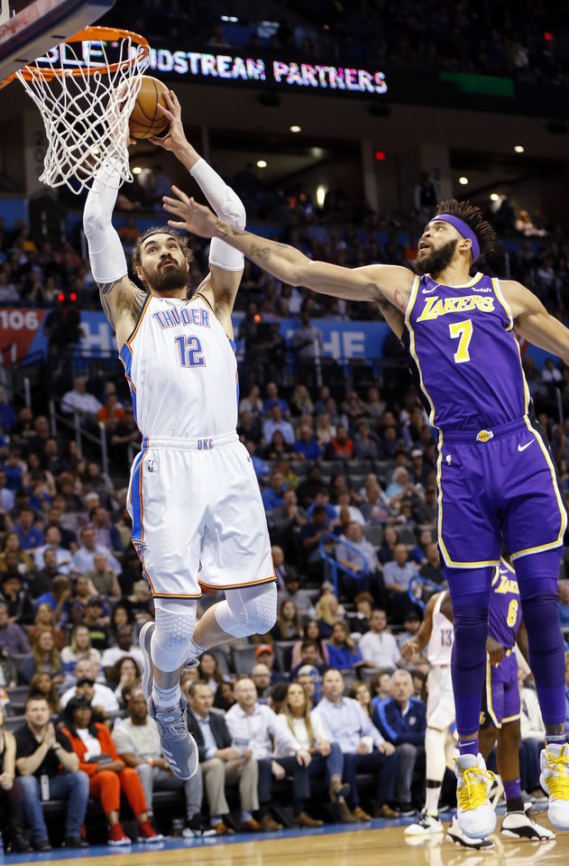 Photo - Oklahoma City's Steven Adams (12) dunks the ball next to Los Angeles' JaVale McGee (7) in the first quarter during an NBA basketball game between the Los Angeles Lakers and the Oklahoma City Thunder at Chesapeake Energy Arena in Oklahoma City, Tuesday, April 2, 2019. Photo by Nate Billings, The Oklahoman