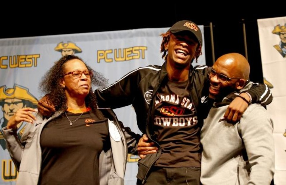 Photo -  Putnam West basketball player Rondel Walker, center, hugs his mother, Angelia, and father, Tracey, after announcing his commitment to Oklahoma State on Thursday. [Sarah Phipps/The Oklahoman]