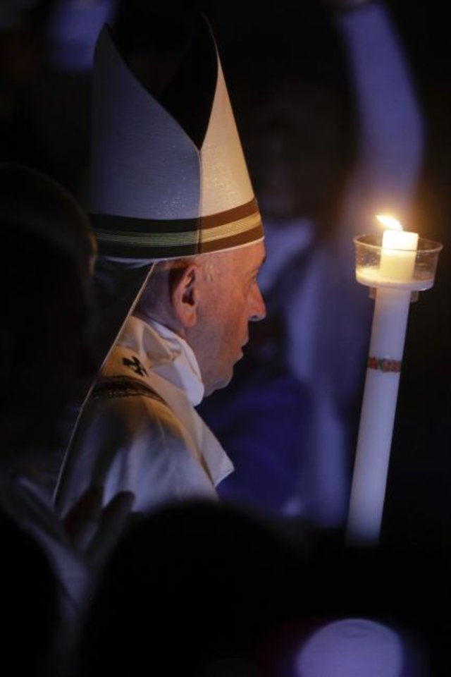 Photo - Pope Francis holds a candle as he presides over a solemn Easter vigil ceremony in St. Peter's Basilica at the Vatican, Saturday, April 21, 2019. (AP Photo/Gregorio Borgia)