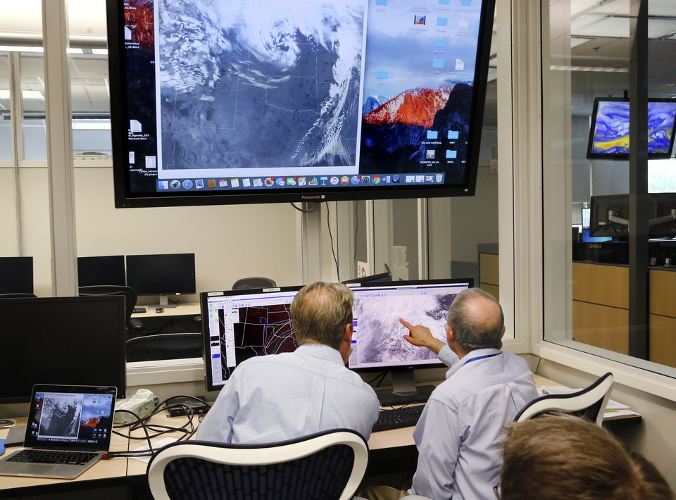 Photo - Meteorologists and forecasters study weather model data Monday, May 20, 2019, at NOAA (National Oceanic and Atmospheric Administration) facility  on the campus of the University of Oklahoma.   [Jim Beckel/The Oklahoman]
