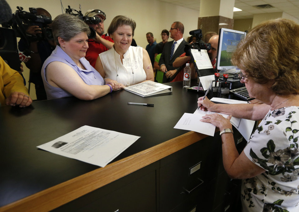 Photo - Sharon Baldwin (left) and Mary Bishop (right), two Tulsa women at the center of a gay marriage case that was appealed to the Supreme Court, accept their marriage license on Monday, October 6, 2014 at the Tulsa County Courthouse in Tulsa, Okla. MATT BARNARD/Tulsa World