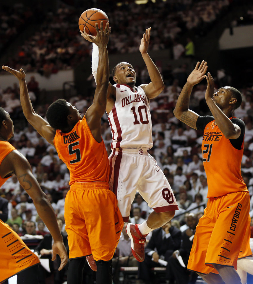 Photo - Oklahoma's Jordan Woodard (10) takes a shot between Oklahoma State's Stevie Clark (5) and Kamari Murphy (21) in the second half during the NCAA men's Bedlam basketball game between the Oklahoma State Cowboys (OSU) and the Oklahoma Sooners (OU) at Lloyd Noble Center in Norman, Okla., Monday, Jan. 27, 2014. OU won, 88-76. Photo by Nate Billings, The Oklahoman