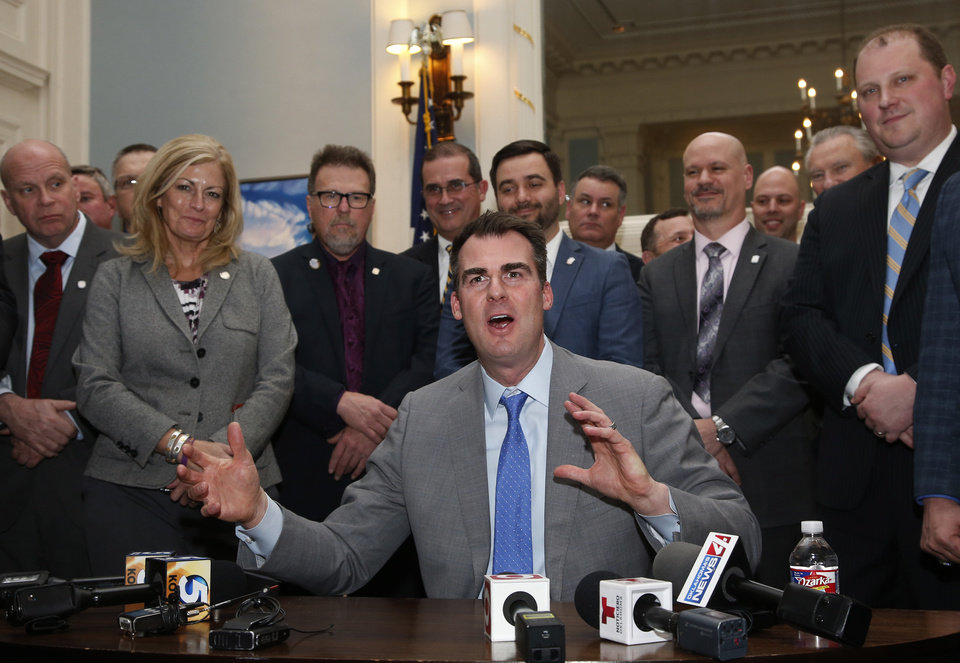 Photo - Oklahoma Gov. Kevin Stitt, surrounded by legislators, answers questions after signing a permitless carry bill into law Wednesday, Feb. 27, 2019, in Oklahoma City. With the new law, Oklahoma residents will be able to openly carry firearms without a background check or training. (AP Photo/Sue Ogrocki)