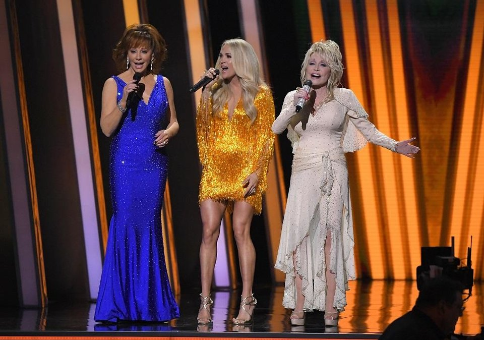 Photo - Hosts Reba McEntire, from left, Carrie Underwood and Dolly Parton appear at the 53rd annual CMA Awards at Bridgestone Arena, Wednesday, Nov. 13, 2019, in Nashville, Tenn. [AP Photo/Mark J. Terrill]