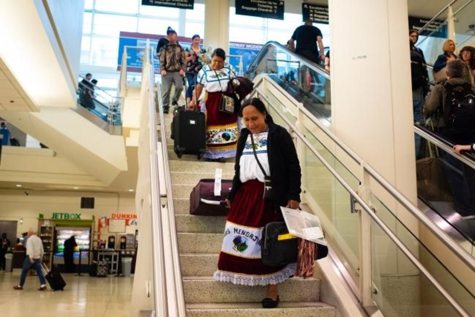 Photo -  María Leonarda Pineda Joaquín, 68, of Cheranastico, Mexico, drags her suitcases down the stairs at Chicago Midway International Airport because she is afraid of the nearby escalators. [Sarah L. Voisin/The Washington Post]