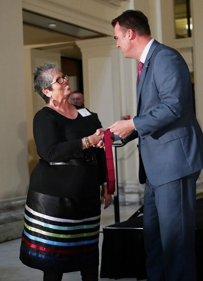 Photo - Juanita Pahdopony receives a Community Service Award from Gov. Kevin Stitt at the Governor's Arts Awards at the Capitol, Tuesday, April 16, 2019. [Photo by Doug Hoke/The Oklahoman]