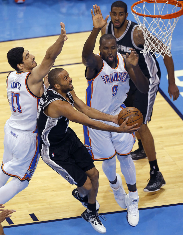 Photo - San Antonio's Tony Parker (9) shoots a lay up in between Oklahoma City's Enes Kanter (11) and Serge Ibaka (9)  during Game 4 of the Western Conference semifinals between the Oklahoma City Thunder and the San Antonio Spurs in the NBA playoffs at Chesapeake Energy Arena in Oklahoma City, Sunday, May 8, 2016. Photo by Sarah Phipps, The Oklahoman