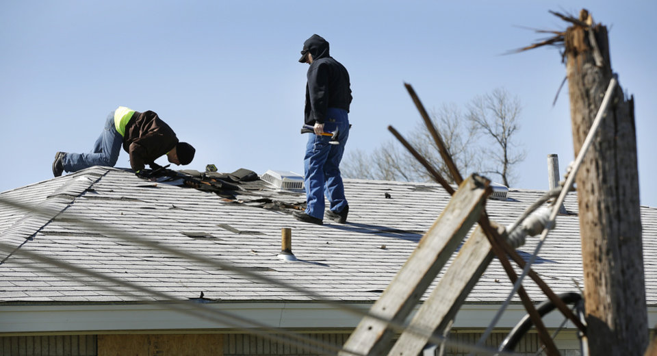 Photo - Shawn Llewellyn, left, and another man prepare to temporarily seal an opening in the roof of his home in a neighborhood  between NW 5 and Main Street, and between Telephone Rd. and Santa Fe in Moore.  The house had been the home where Llewellyn's  mother lived before her death earlier this month. Thursday morning, March 26, 2015, the day after a tornado damaged homes and a school Wednesday evening. Photo by Jim Beckel, The Oklahoman