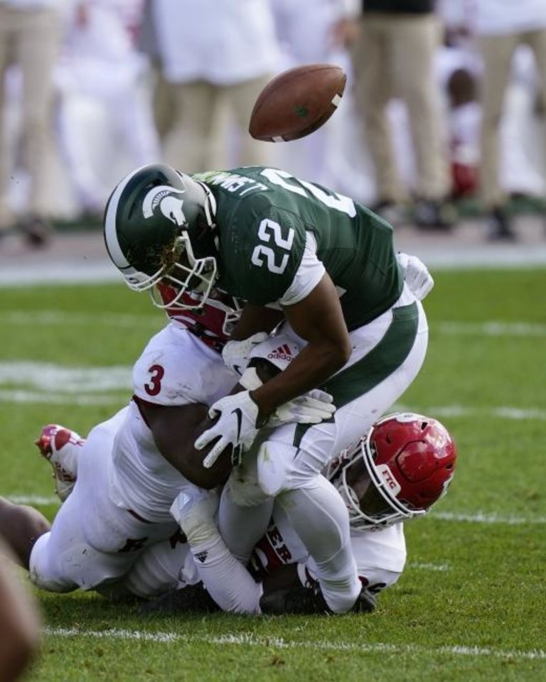 Photo -  Rutgers linebacker Olakunle Fatukasi (3) knocks the ball away from Michigan State running back Jordan Simmons (22) during the second half of a 38-27 win Saturday in East Lansing, Mich. [AP Photo/Carlos Osorio]