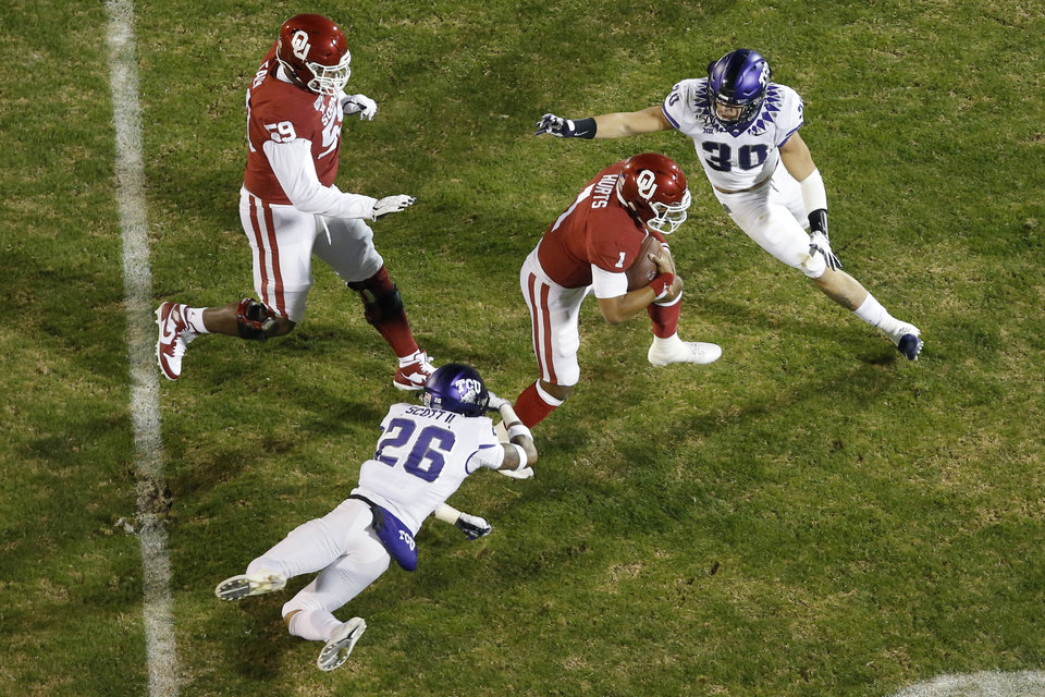 Photo - Oklahoma's Jalen Hurts (1) runs past TCU's Garret Wallow (30) and Vernon Scott (26) during an NCAA football game between the University of Oklahoma Sooners (OU) and the TCU Horned Frogs at Gaylord Family-Oklahoma Memorial Stadium in Norman, Okla., Saturday, Nov. 23, 2019. [Bryan Terry/The Oklahoman]