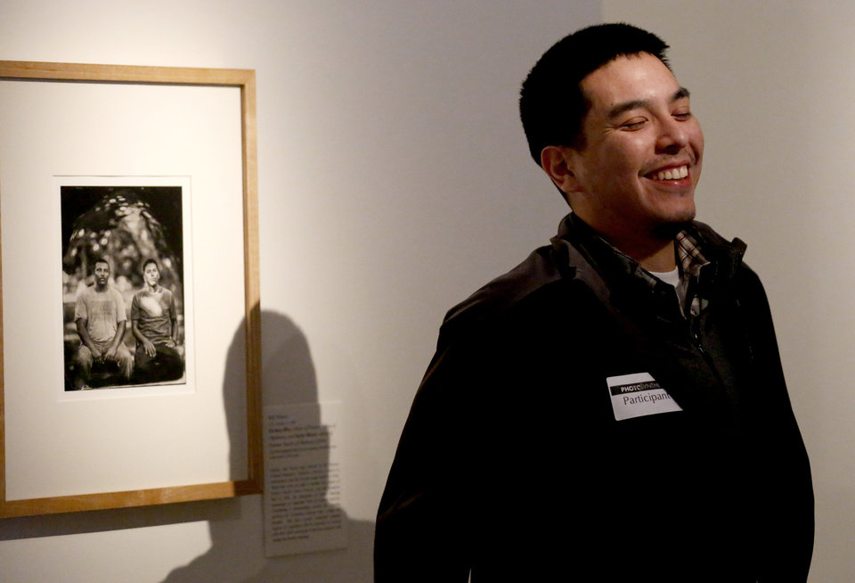 Photo -  Taylor Moore takes a photos next to his tintype in Will Wilson's Photo/synthesis exhibition of tintypes photographs of American Indians at the Fred Jones Jr. Museum of Art. The exhibition was funded through a grant from the National Endowment for the Arts. Some in Oklahoma's arts community worry about the fate of that agency under the Trump administration. Photo by Sarah Phipps, The Oklahoman