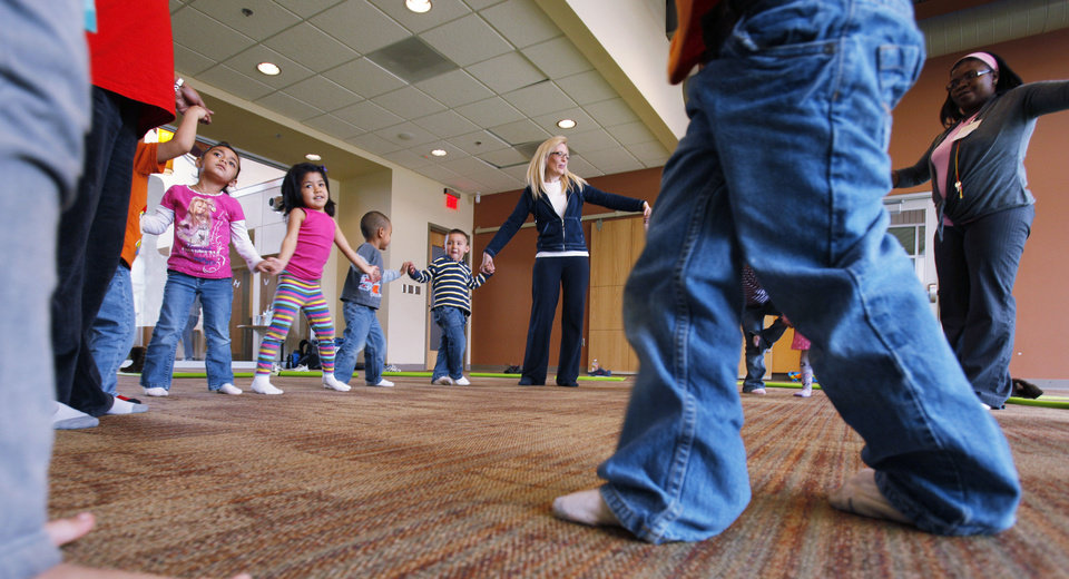 Photo - Left: Angela Moorad teaches yoga to 3- and 4-year-olds Wednesday.