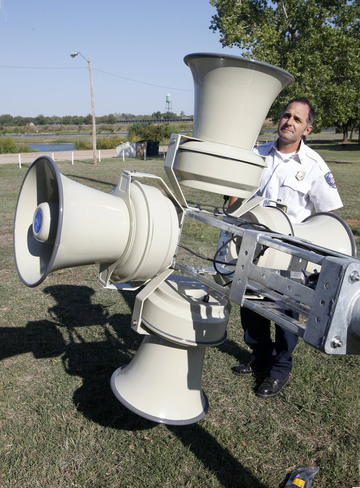 Photo - Maj. Brandon Pursell of the Del City Fire Department looks at a new siren being installed at Eagle Lake.
