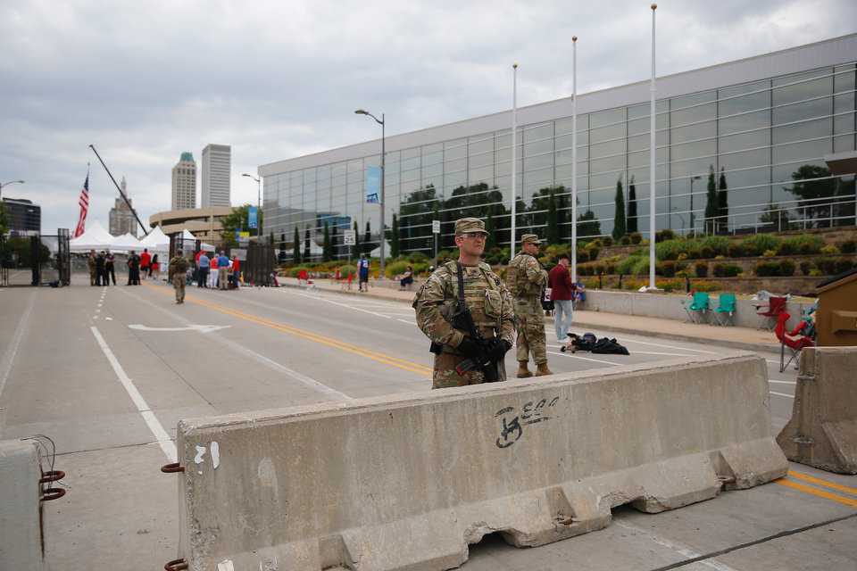 Photo - State and local police and members of the Oklahoma National Guard stand ready in downtown Tulsa during the Trump 2020 rally Saturday morning, June 20, 2020. [Sarah Phipps/The Oklahoman]