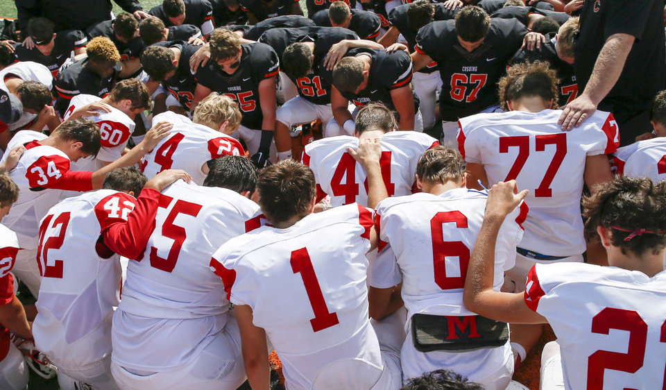 Photo -  McLoud and Cushing players pray together Saturday before a high school football at O'Dell Field in Cushing.  [Photo by Nate Billings, The Oklahoman]