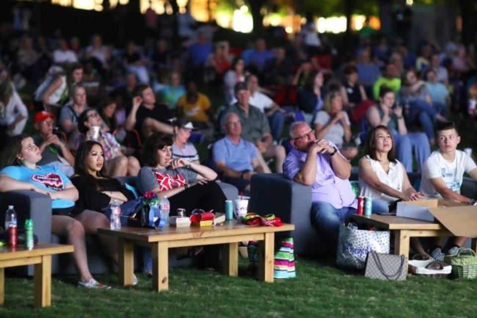 Photo -  A crowd watches an outdoor screening of the Paul George documentary
