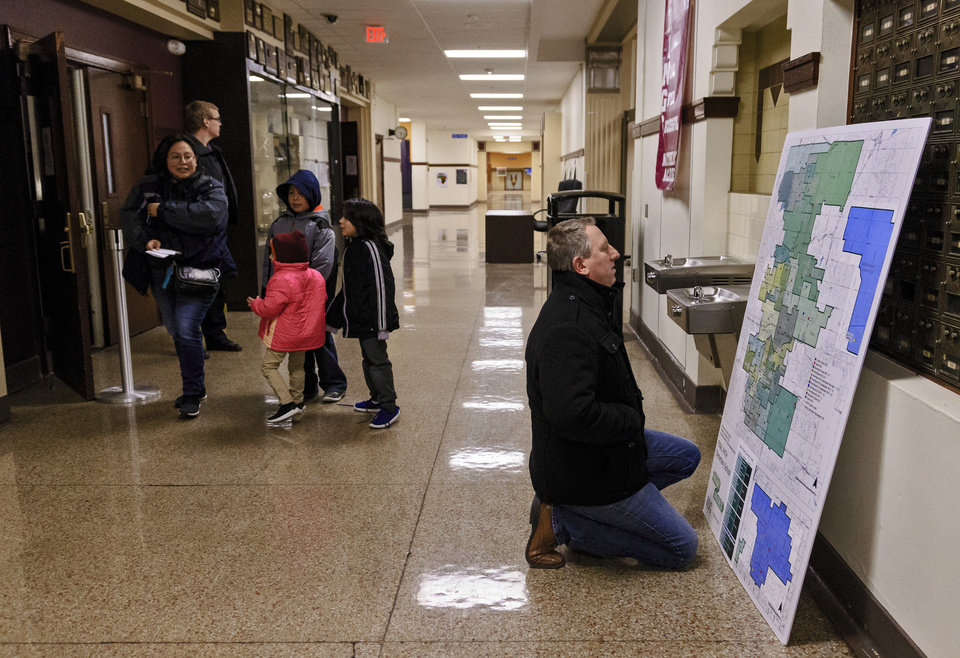 Photo -  Mitch Ruzzoli looks over one of the new school maps after the Oklahoma City Public School special meeting to vote on the Pathway to Greatness plan to close 15 schools and reconfigure or relocate 17 others at Northeast Academy in Oklahoma City, Okla. on Monday, March 4, 2019. The school board voted in favor to move forward with the proposed plan.   Photo by Chris Landsberger, The Oklahoman