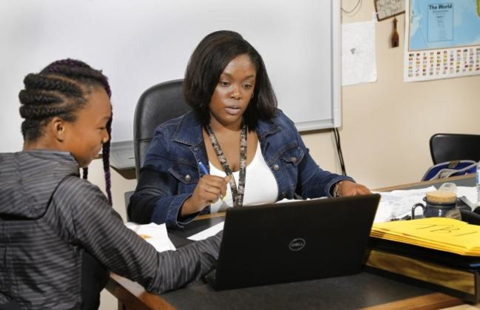 Photo -  Mauri Hubbard, right, looks over an assignment with her student Keosha Jackson in Hubbard's classroom at Douglass High School. [Jim Beckel/The Oklahoman]
