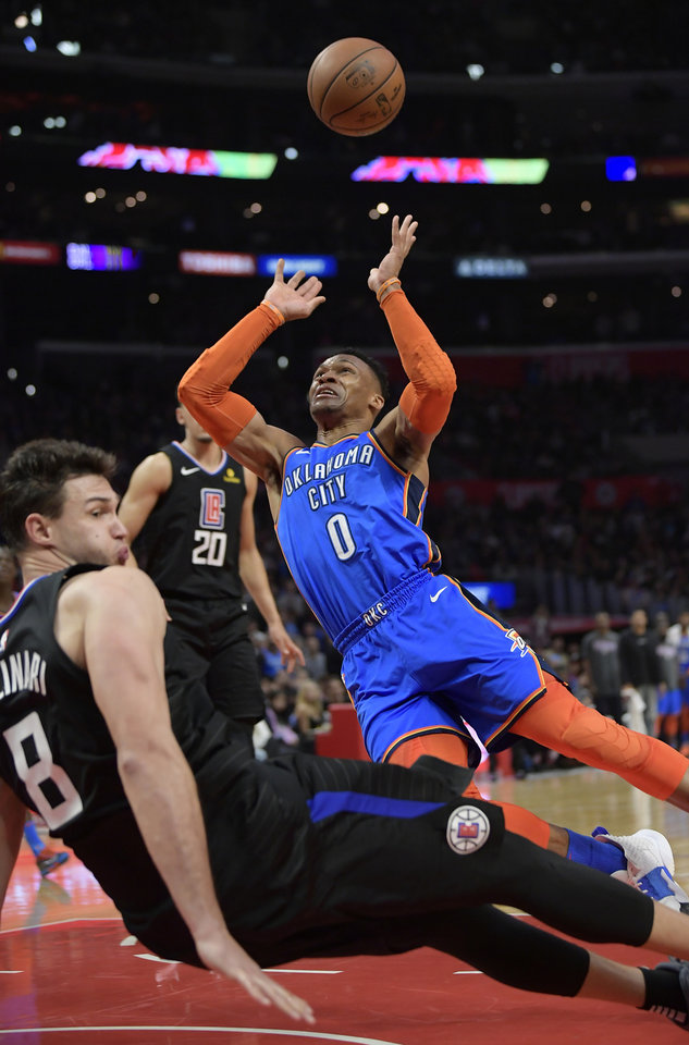 Photo - Oklahoma City Thunder guard Russell Westbrook, right, shoots after charging into Los Angeles Clippers forward Danilo Gallinari, left, during the second half of an NBA basketball game Friday, March 8, 2019, in Los Angeles. Westbrook was charged with his sixth foul on the play. The Clippers won 118-110. (AP Photo/Mark J. Terrill)