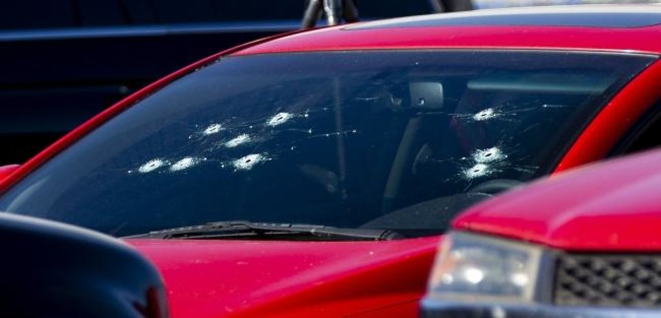Photo -  Bullet holes in the windshield of a car at the scene of a shooting that left three people dead in the Walmart parking lot in Duncan on Monday. [Chris Landsberger/The Oklahoman]