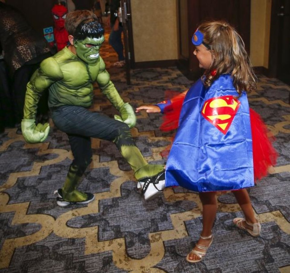 Photo -  Twins Harry Hart, 7, as the Incredible Hulk, and Mia Hart, 7, as Supergirl, play fight Friday before entering the Sidekicks Ball for kids at the Oklahoma Institute for Child Advocacy's Heroes Ball. [Nate Billings/The Oklahoman]