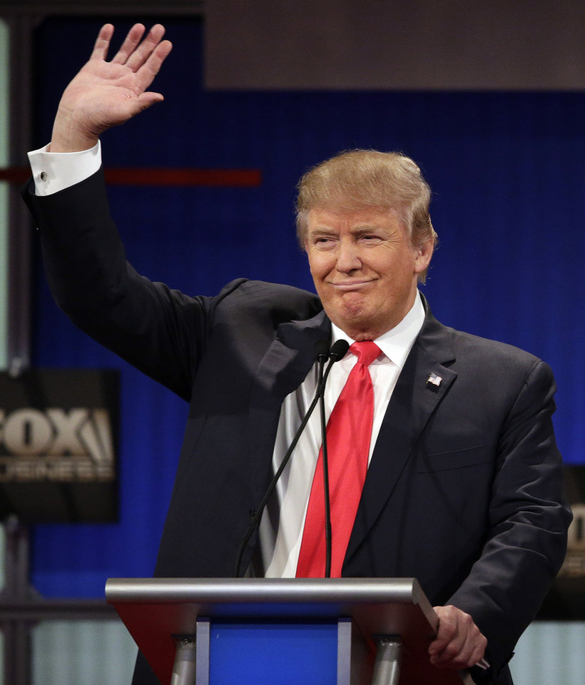 Photo - Republican presidential candidate, businessman Donald Trump waves during the Fox Business Network Republican presidential debate at the North Charleston Coliseum, Thursday, Jan. 14, 2016, in North Charleston, S.C. (AP Photo/Chuck Burton)