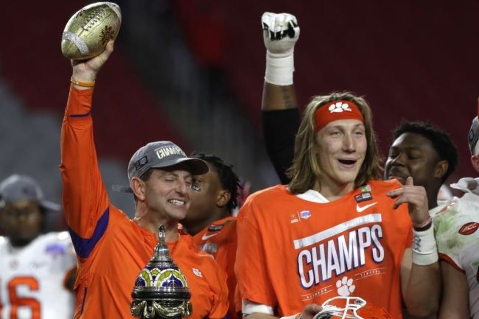 Photo -  Clemson coach Dabo Swinney, left, and quarterback Trevor Lawrence celebrate their Fiesta Bowl victory over Ohio State. The Tigers will face LSU at 7 p.m. Monday for the national championship. [AP PHOTO]