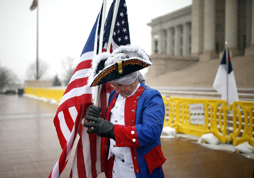 Photo - A man, who refused to give his name, stands in front of the state Capitol in Oklahoma City Friday, Feb. 27, 2015. He said he was there to support the flag. Photo by Sarah Phipps, The Oklahoman