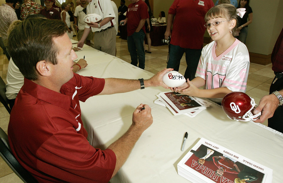 Photo - OU, FANS, AUTOGRAPH: University of Oklahoma college football head coach Bob Stoops autographs a football for 9-year-old Carlie Hasty (CQ CARLIE HASTY) during the Sooner Caravan at the National Cowboy and Western Heritage Museum in Oklahoma City, August 03, 2006.  Steve Gooch /The Oklahoman