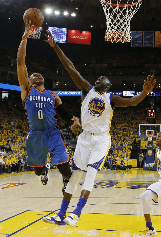 Photo - Oklahoma City's Russell Westbrook (0) shoots against Golden State's Draymond Green (23) in the first half during Game 2 of the Western Conference finals in the NBA playoffs between the Oklahoma City Thunder and the Golden State Warriors at Oracle Arena in Oakland, Calif., Wednesday, May 18, 2016. Golden State won 118-91. Photo by Nate Billings, The Oklahoman