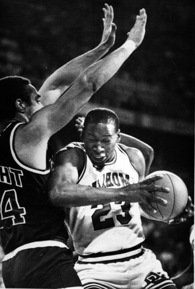 Photo - Former OU basketball player Wayman Tisdale. Oklahoma's Wayman Tisdale (23) grimaces as he slams an elbow into Kansas center Kelly Knight beneath OU's basket in the first half of the Big Eight Conference title game Saturday night. No foul was called on the play. Photo taken unknown, Photo published 3/11/1984 in The Daily Oklahoman. ORG XMIT: KOD