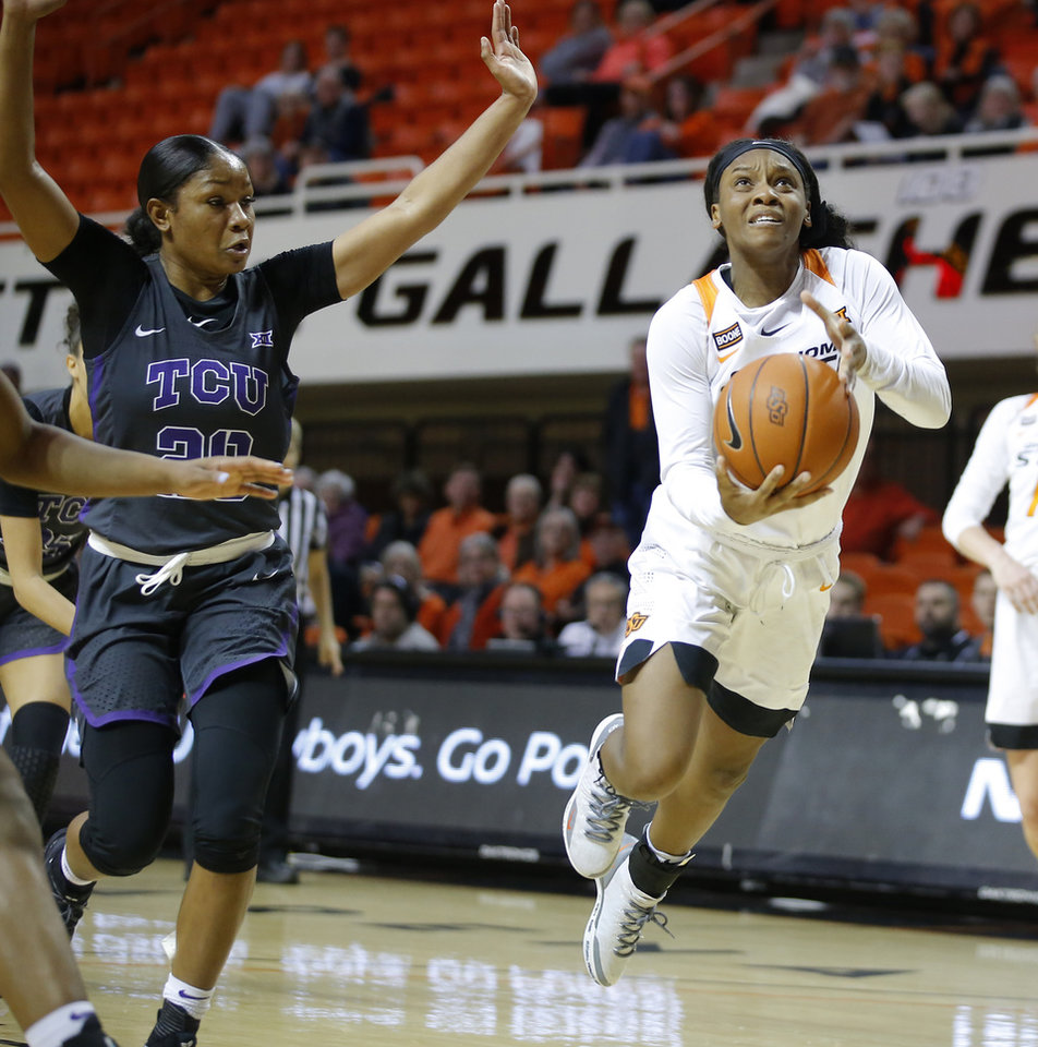 Photo - Oklahoma State's Ja'Mee Asberry (21) goes past TCU's Lauren Heard (20) during a women's NCAA basketball game between the Oklahoma State University Cowgirls (OSU) and the TCU Horned Frogs at Gallagher-Iba Arena in Stillwater, Okla., Wednesday, Jan. 29, 2020. Oklahoma State lost 72-68. [Bryan Terry/The Oklahoman]