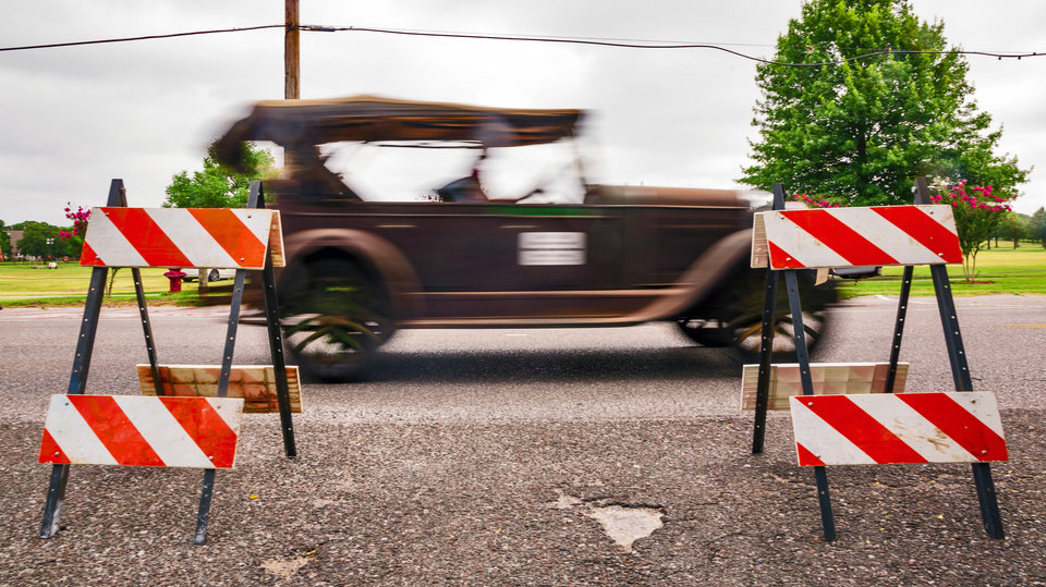 Photo - A vintage cars drive past road blocks as it  makes its way to staging for the Bethany Freedom Festival parade in Bethany, Okla. on Thursday, July 4, 2019.    [Chris Landsberger/The Oklahoman]