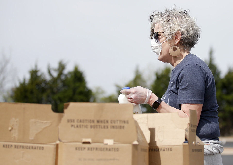 Photo - Cheryl Boylow loads groceries into cars at PeopleÕs Church, 800 E. Britton Rd., in Oklahoma City, Thursday, April 9, 2020. Cars lined up for miles for hours as the church members gave away 6,000 pounds of free groceries and supplies. [Sarah Phipps/The Oklahoman]