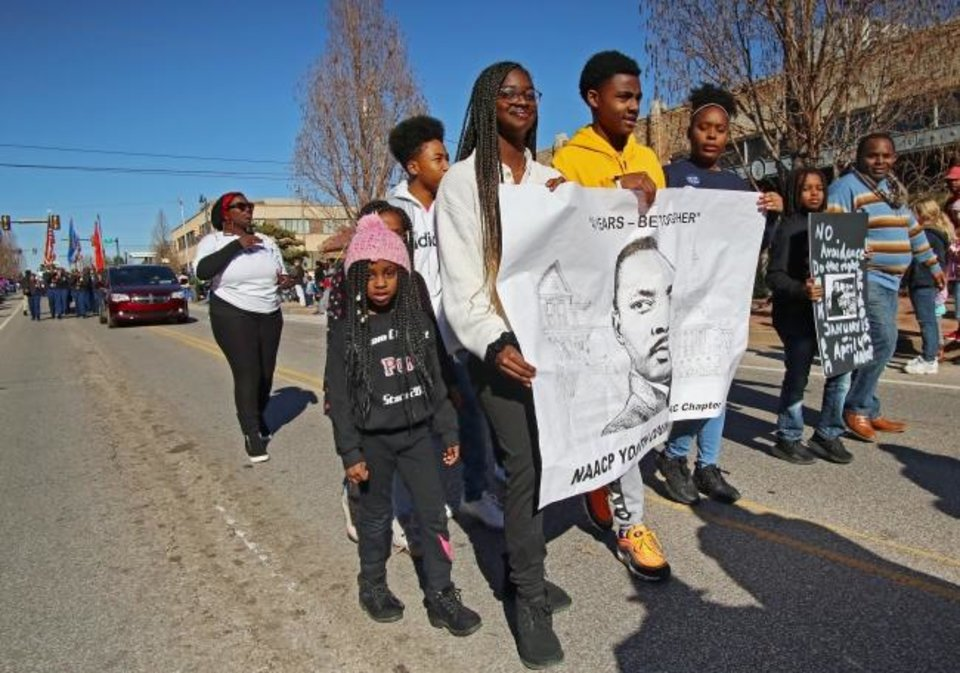 Photo -  Several members of the NAACP Youth Council hold a banner featuring an image of Martin Luther King Jr. during the 2020  Martin Luther King Holiday Parade. [Doug Hoke/The Oklahoman]